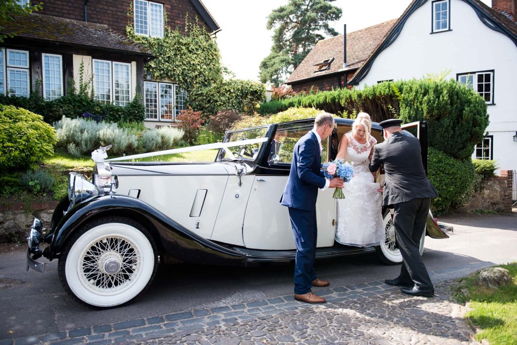 Elegant bride steps off vintage car