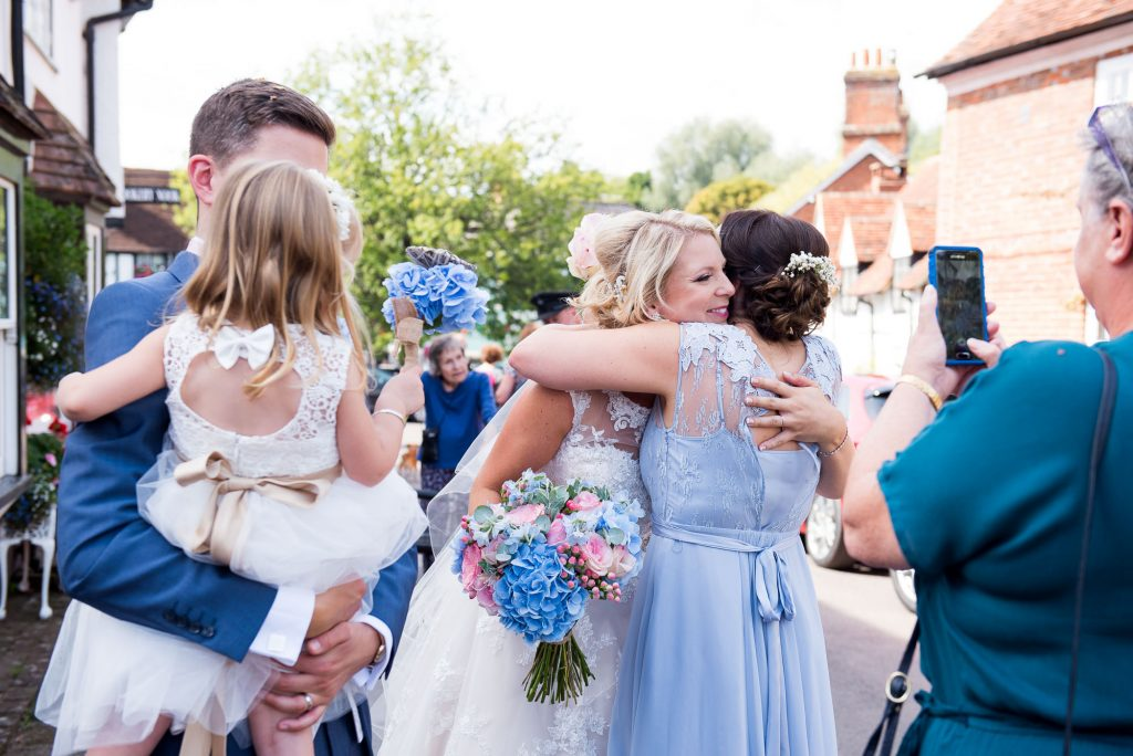 Bridesmaid congratulates bride after wedding ceremony