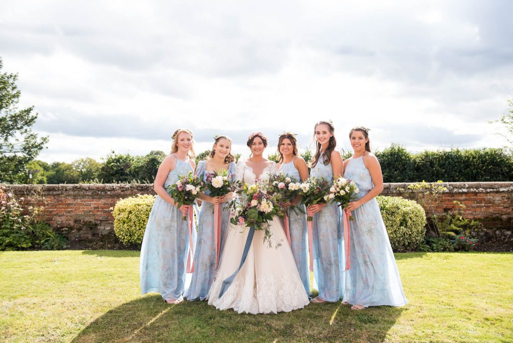 Jay West Bride with pastel blue bridesmaids holding bouquet by Flowers at The Forge Norfolk