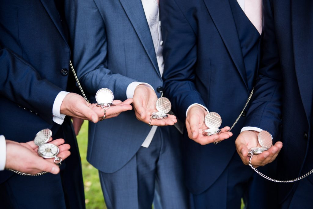 Groom with best man holding matching pocket watches