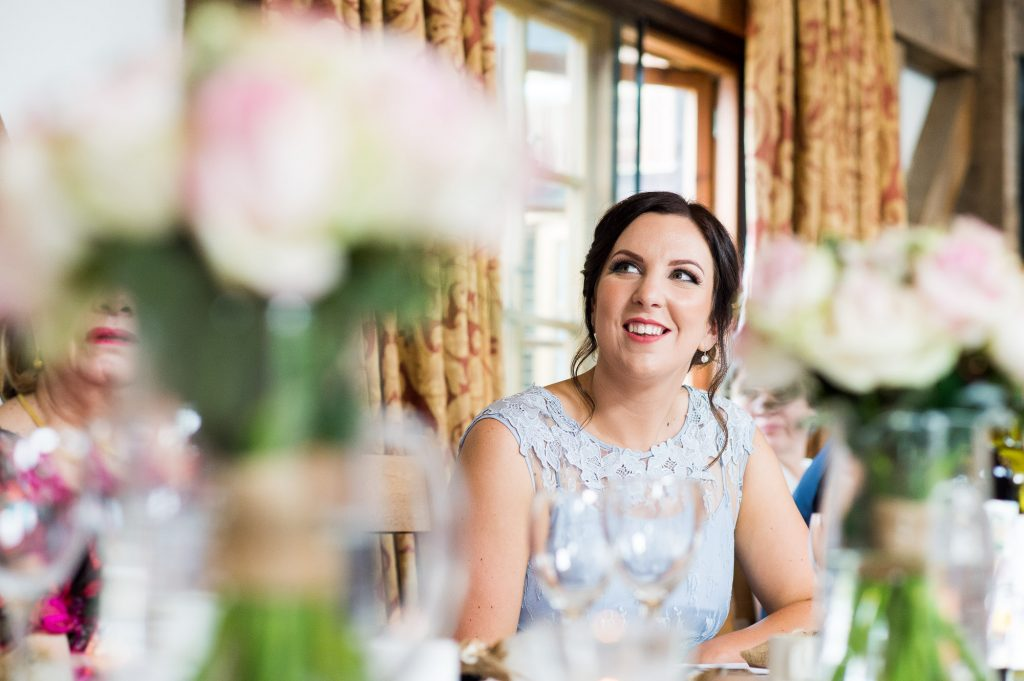 Natural bridesmaid listening during wedding speech Barn wedding