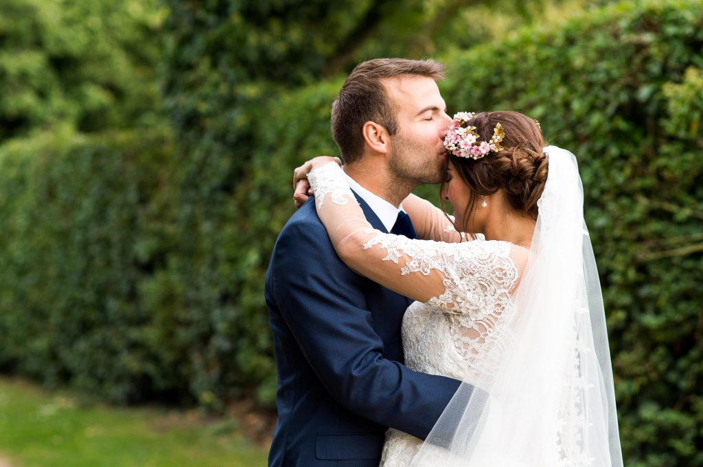 Bride wearing Jay West Bridal dress with floral headband with groom wearing Calvin Klein Norfolk