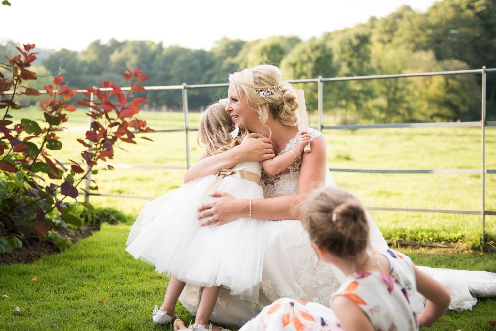 Elegant bride hugging flower girl countryside wedding