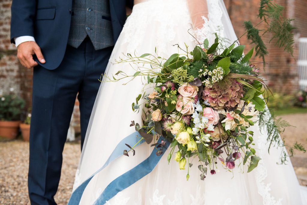 Creative wedding portrait photography with bridal bouquet by Flowers at The Forge Norfolk