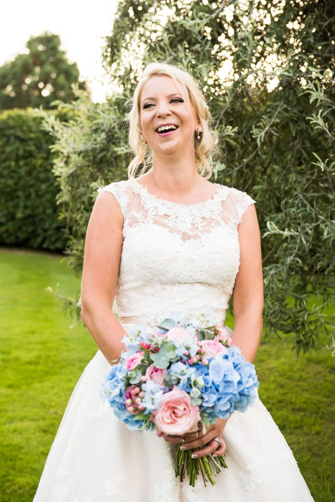 Laughing natural bride wearing Mae Bridal Boutique Ronald Joyce