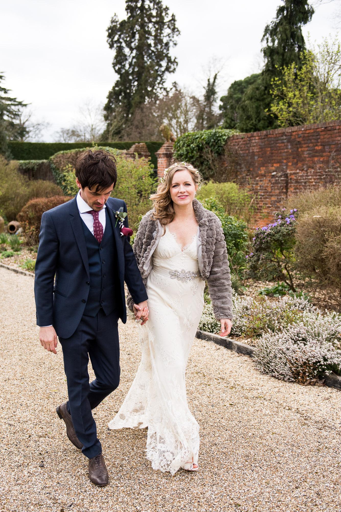 bride and groom walk hand in hand Essex Barn Wedding