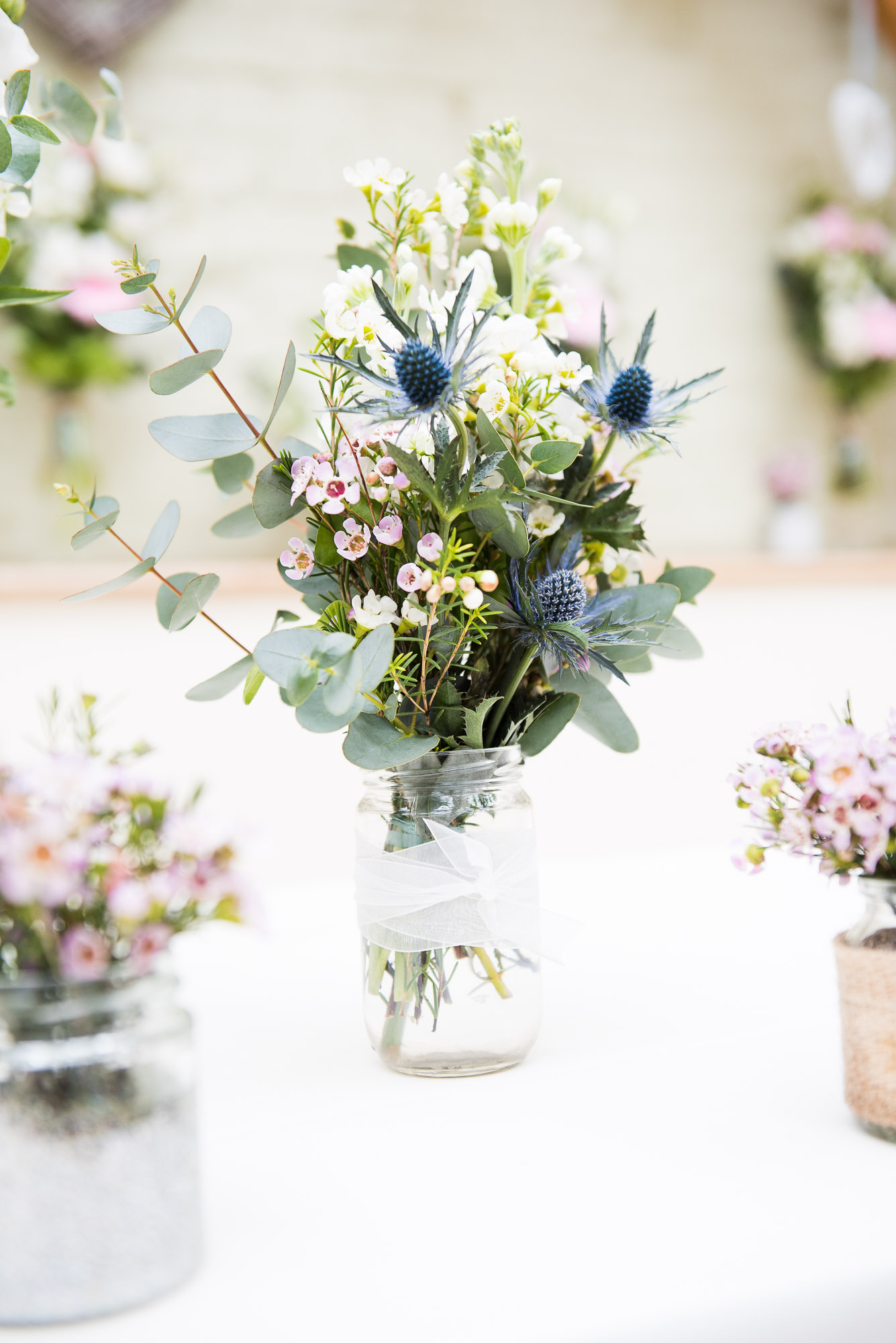 Spring floral tones of eucalyptus and sea holly in floral arrangement