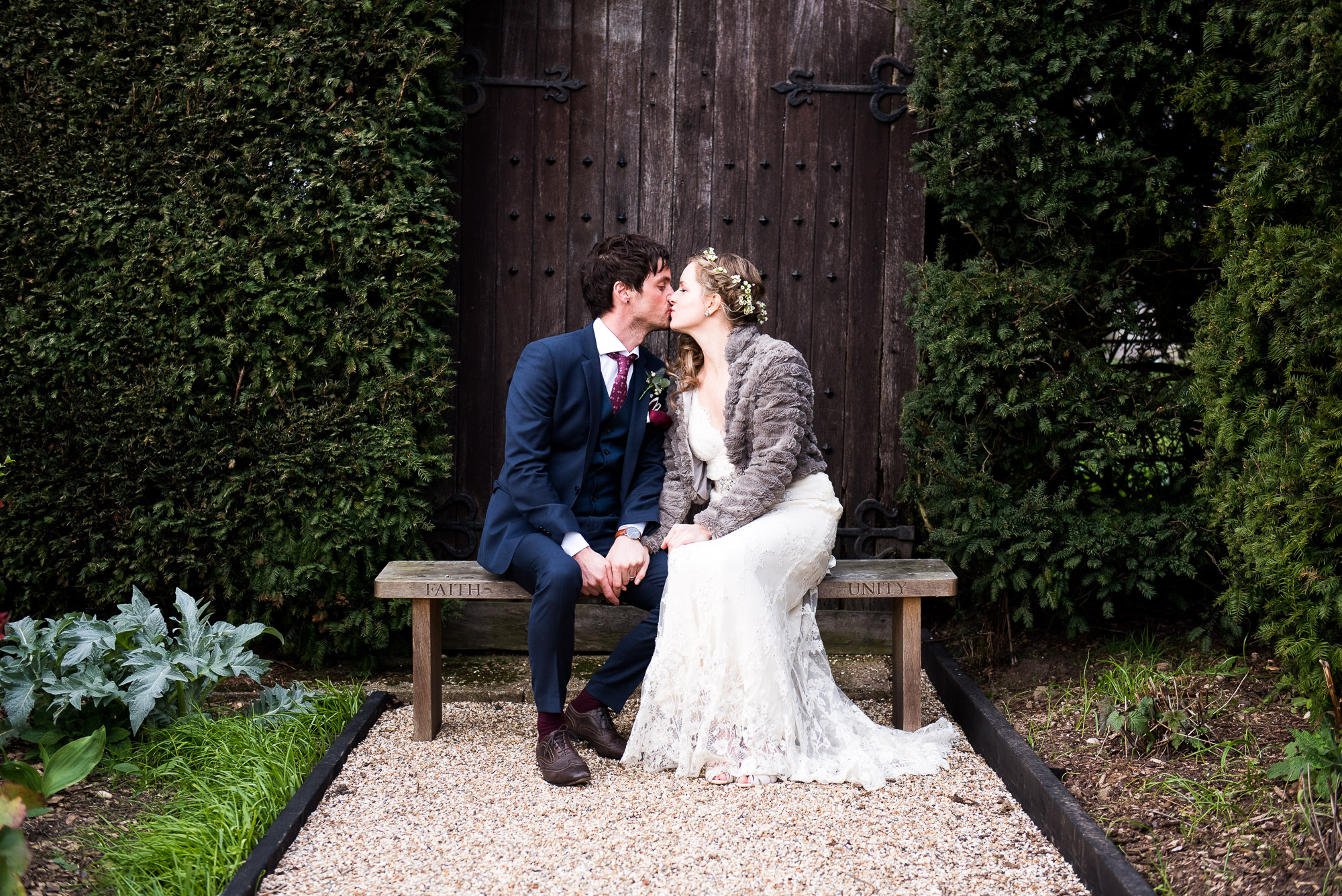 boho bride and groom wearing blue suit sharing a kiss