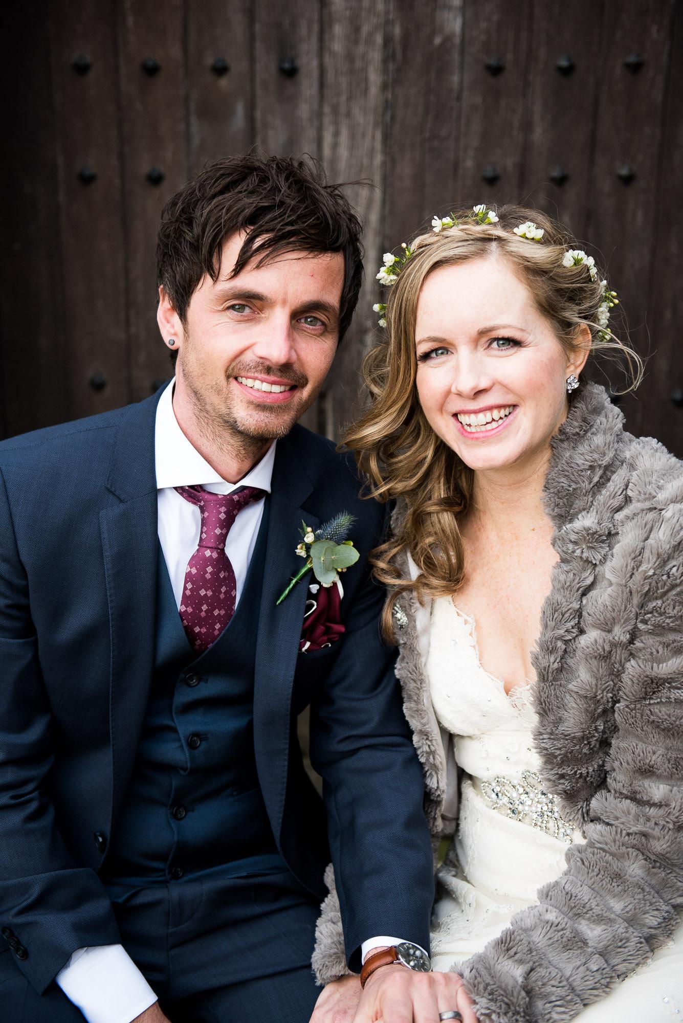 Smiling bride with groom Essex Barn wedding