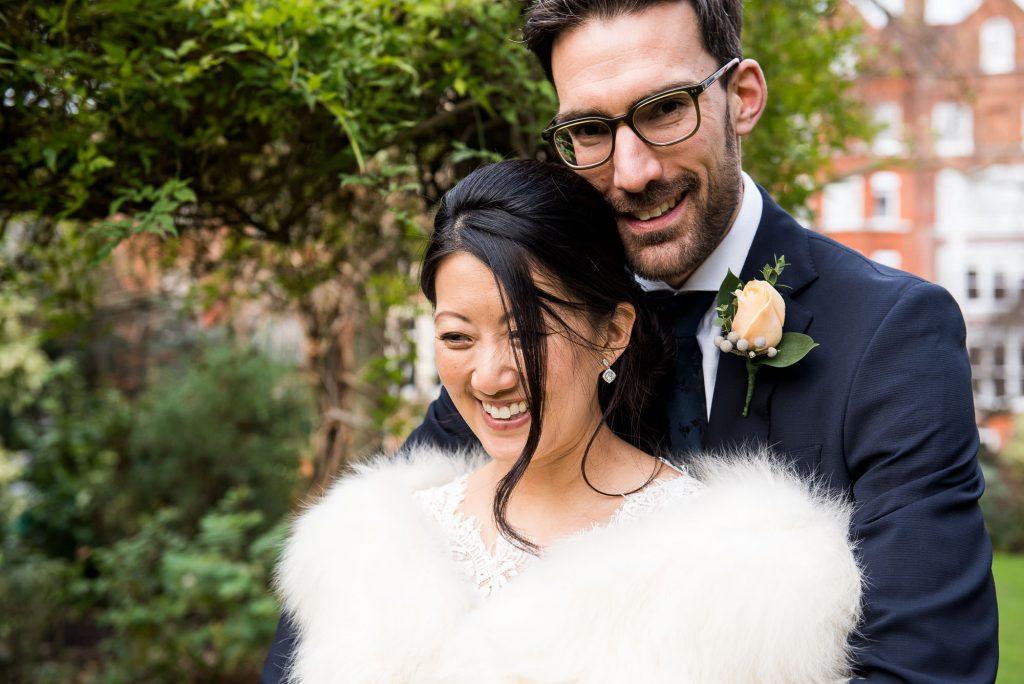 Smiling groom embracing his bride London wedding