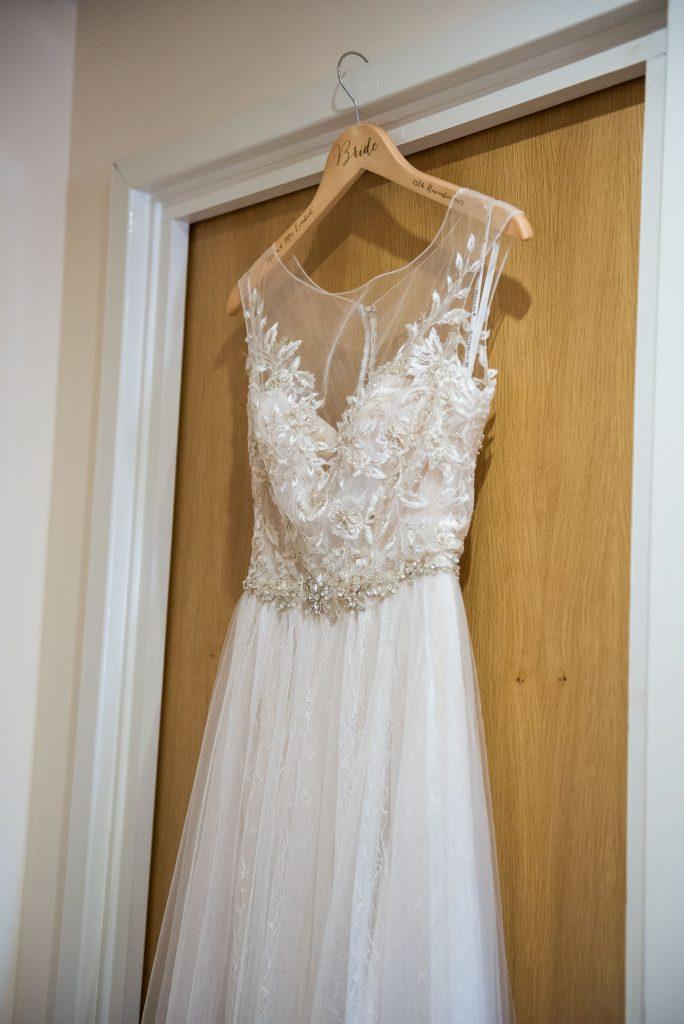 Ashridge House Wedding. Natural Wedding Photography. Bridal preparation Berkhamstead Brides dress hanging in doorway.