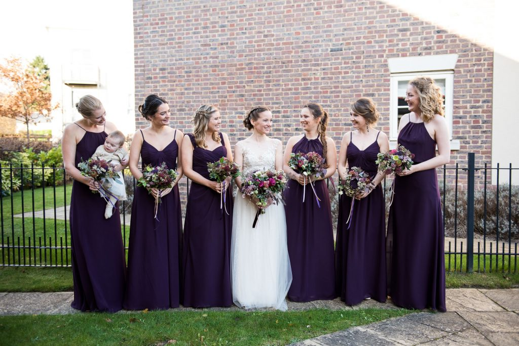 Ashridge House Wedding. Natural Wedding Photography. Bride surrounded by her bridesmaids with Winter wedding purple colours.