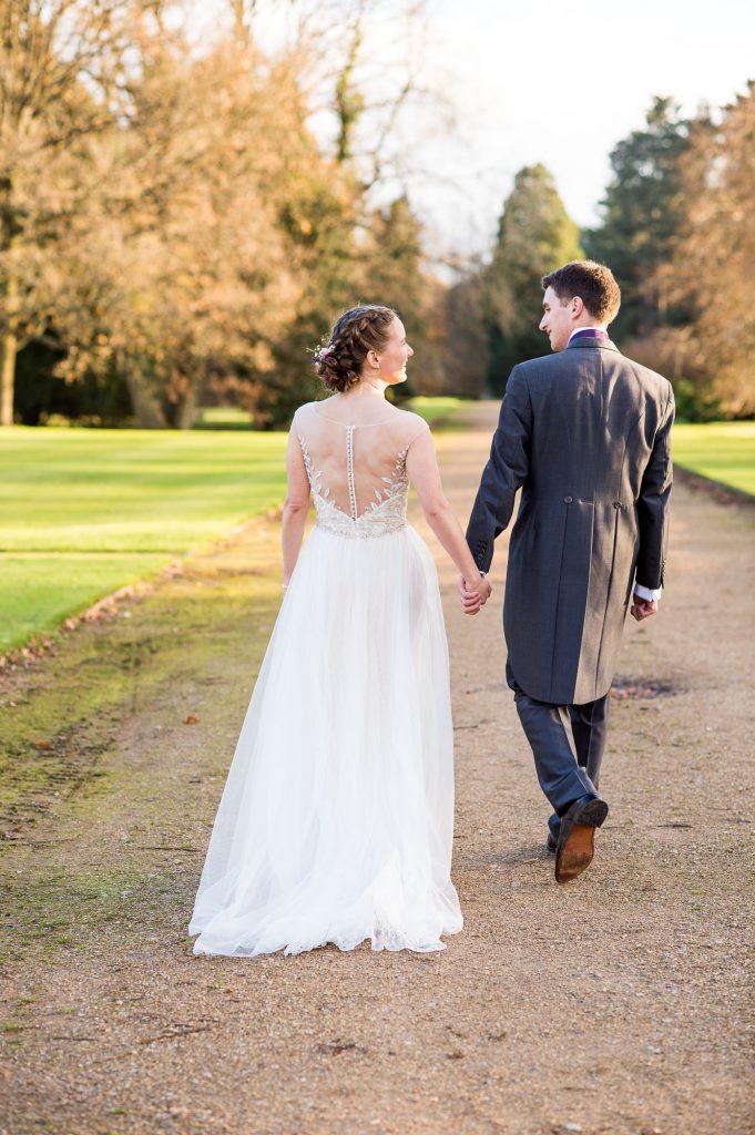 Ashridge House Wedding. Natural Wedding Photography. Golden hour evening light portrait of relaxed bride and groom walking in Ashridge estate.