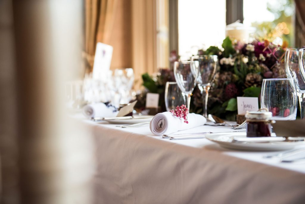 Ashridge House Wedding. Natural Wedding Photography. Natural floral tone centre pieces with pine cones, winter berries, moss and pink peppercorn favours.