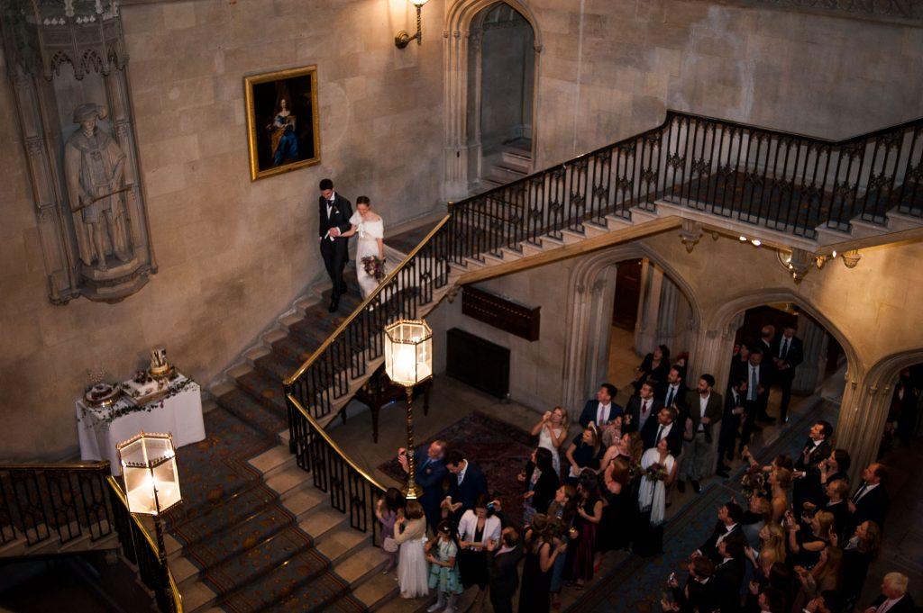 Ashridge House Wedding. Natural Wedding Photography. Couple walk down the grand staircase for their confetti line.