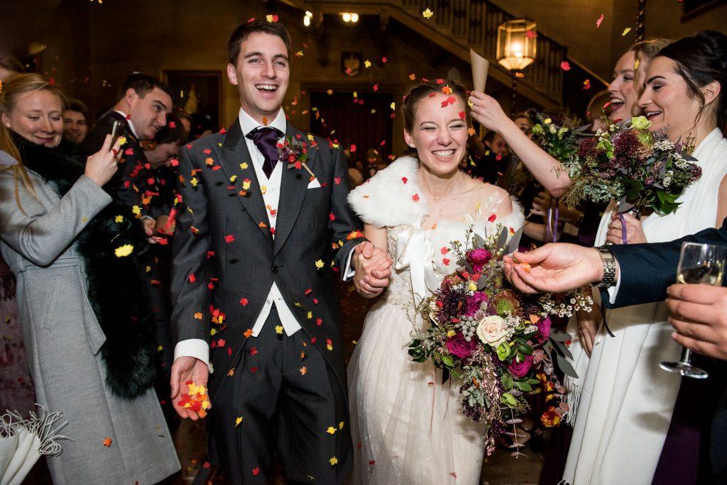 Ashridge House Wedding. Natural Wedding Photography. Captured natural moment of couple walking through confetti.