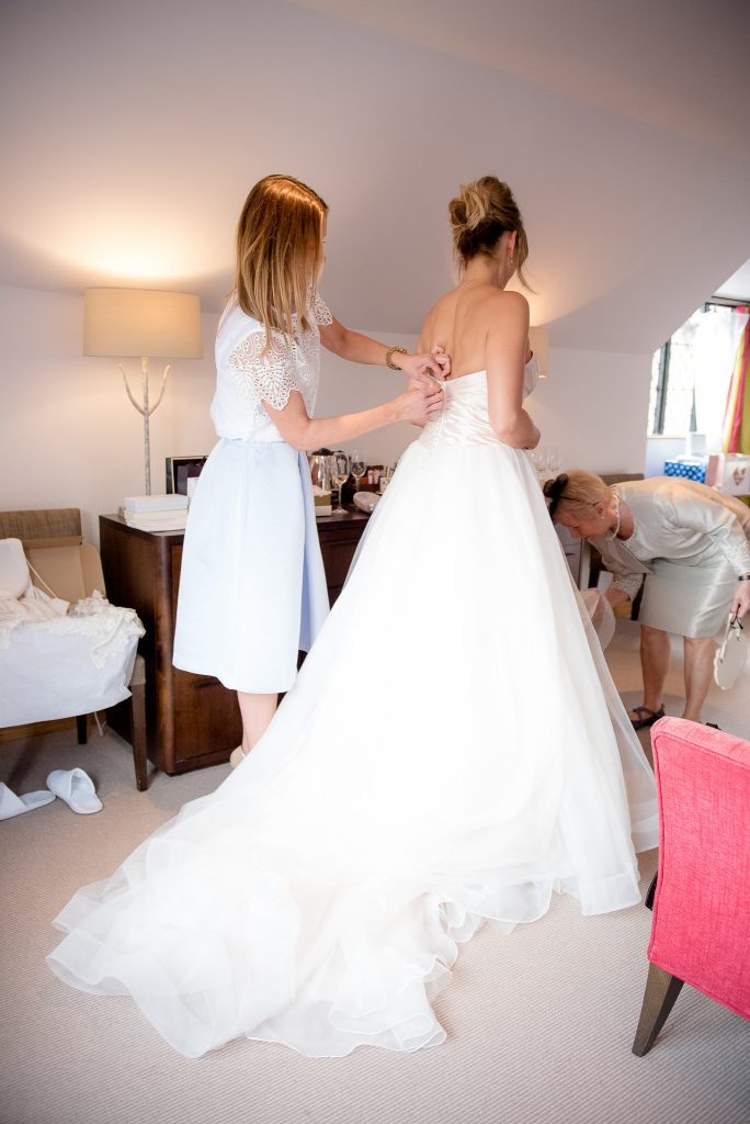 Great Fosters. Natural Wedding Photography. The Bride is Helped into her Ellis Bridal Wedding Dress.