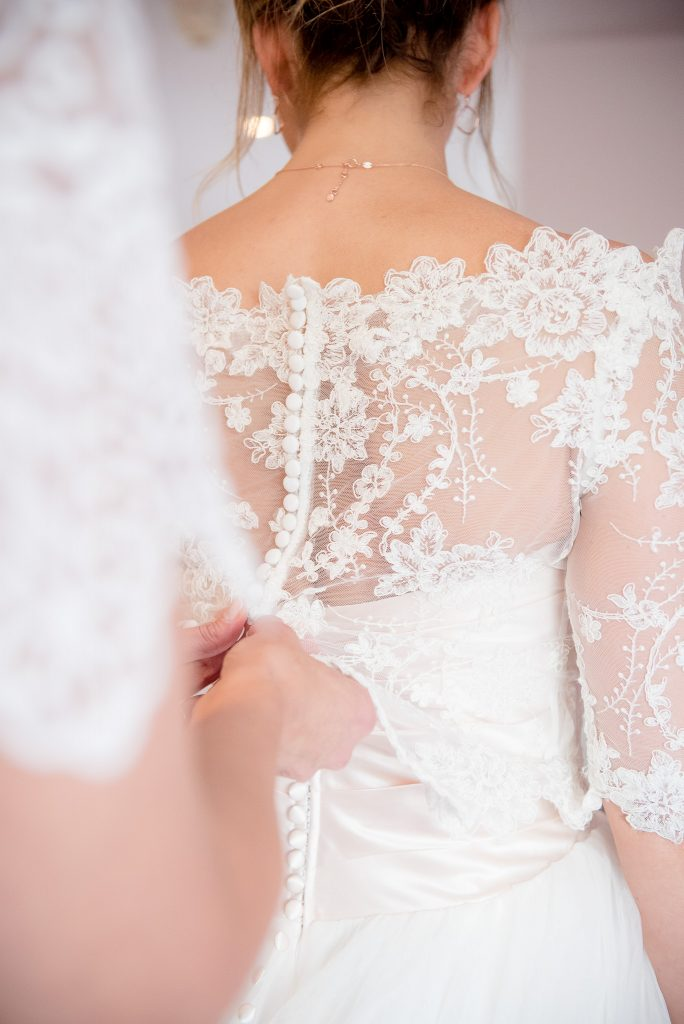 Great Fosters. Natural Wedding Photography. The Bride is Helped into her Ellis Bridal Wedding Dress and Lace Shrug.