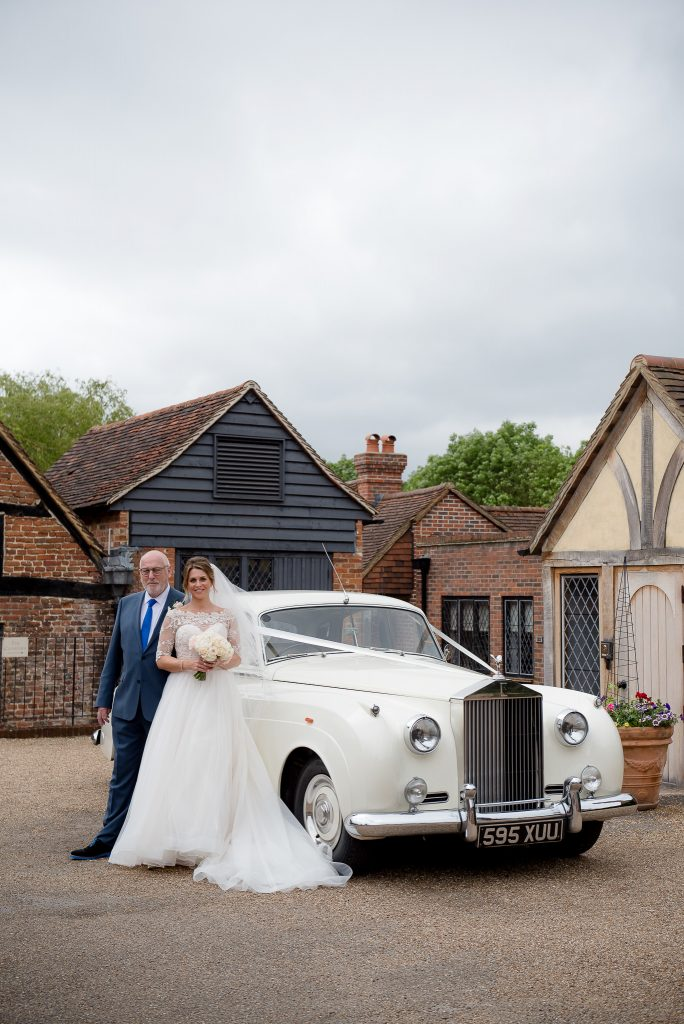 Great Fosters. Natural Wedding Photography. The Bride poses in Front of The Wedding Car With her Father.