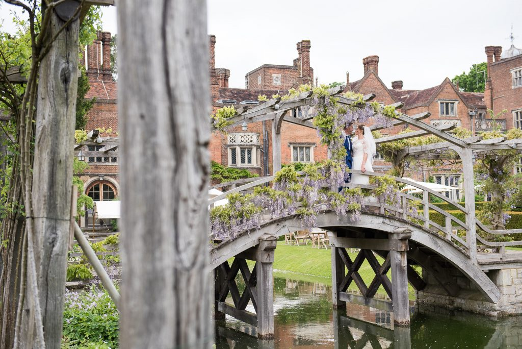 Great Fosters. Natural Wedding Photography Surrey. Couple embrace on the old wooden wisteria bridge at Great Fosters.