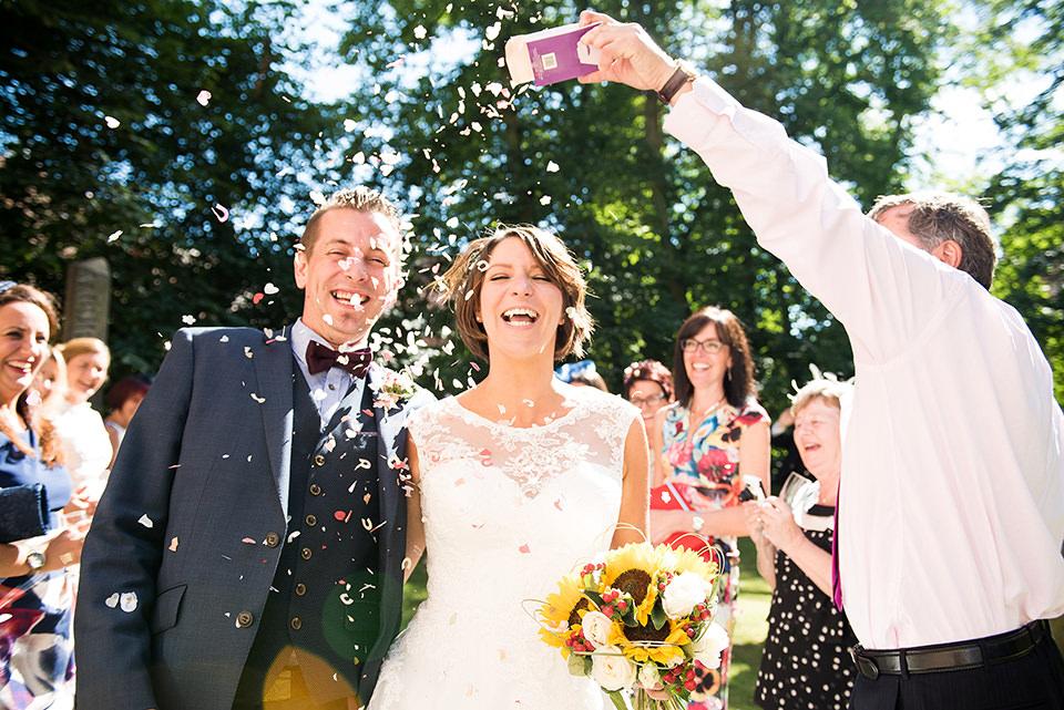 Wedding Confetti, Documentary Wedding Photography Surrey, Couple Laughing as They Walk Down Confetti Line