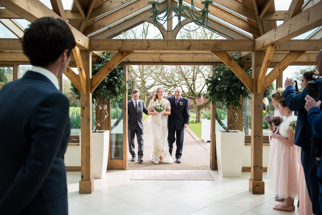 Wedding Day Timeline - Bride Walking Down the Aisle With Her Two Dads - Outdoor Surrey Wedding