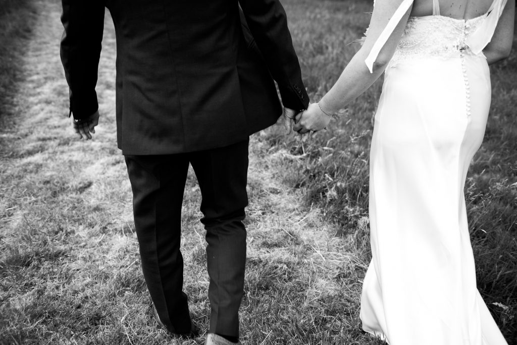 Outdoor Wedding Ceremony, Surrey Wedding Photography, Black and White Photograph Bride and Groom Walk Together In A Field