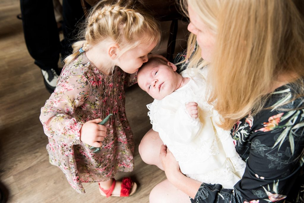 LGBT wedding photography, candid moment where sister kisses her newborn sibling on the head