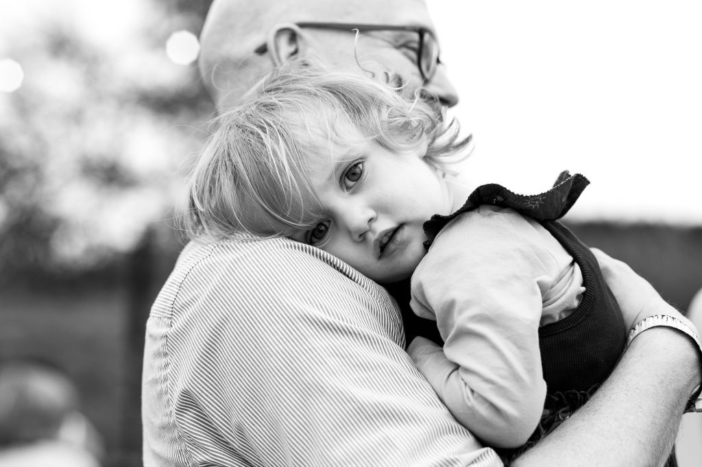 LGBT wedding photography, gorgeous little girl cuddles her father on his shoulder