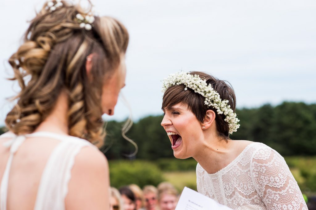 LGBT wedding photography, bride laughing out loud during wedding vows