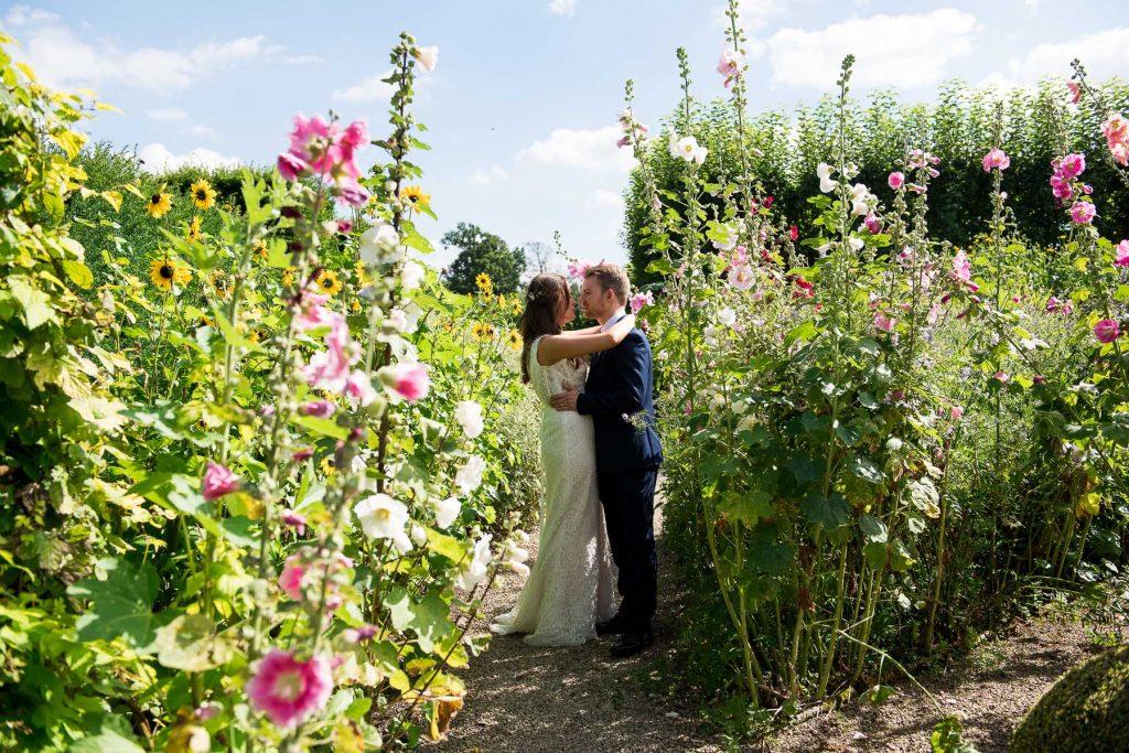 Bride and groom amongst flowers Loseley Park wedding