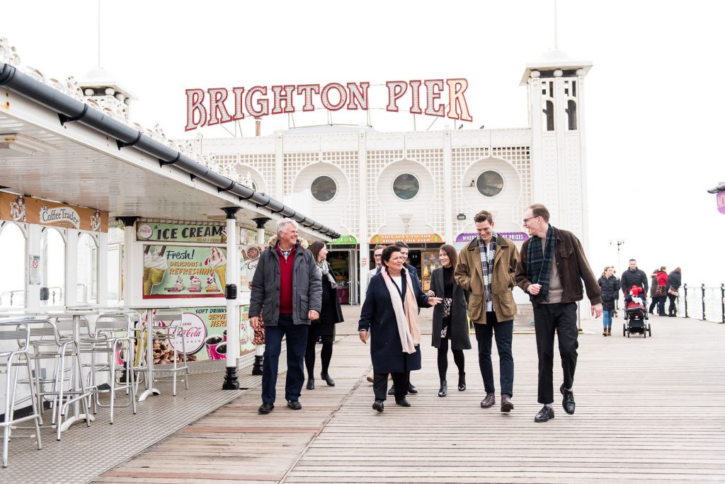 LGBT wedding photography, family walk down Brighton beach pier chatting
