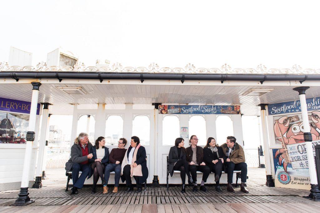 LGBT wedding photography, family sit on Brighton beach pier chatting