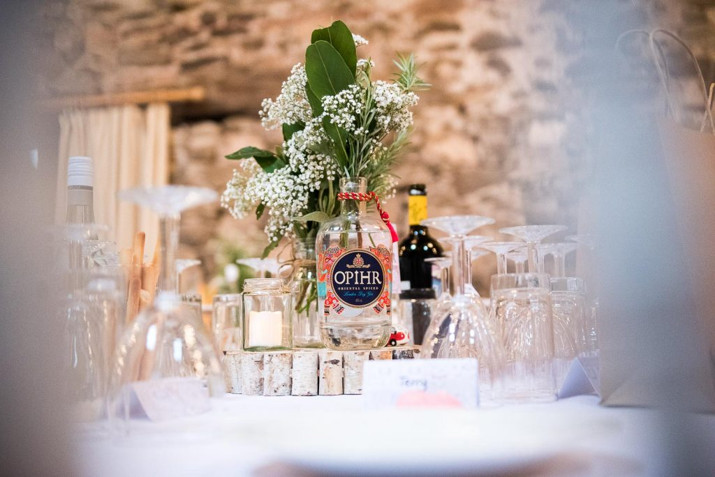Alternative wedding photography - vintage and collected gin bottle vases