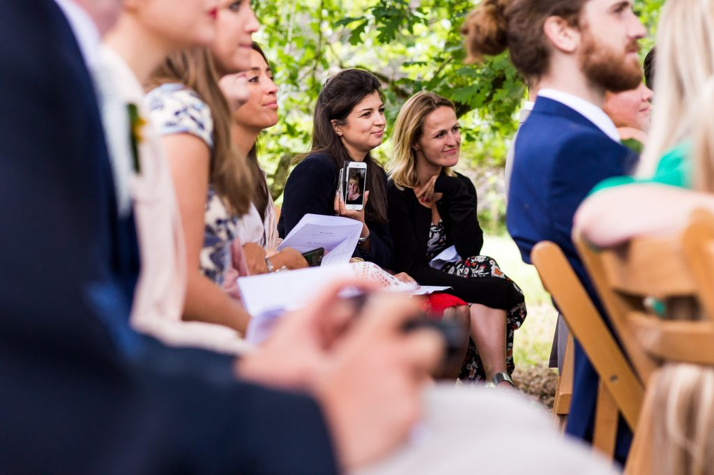 LGBT wedding photography, outdoor wedding cermony guest holds phone with friend on facetime