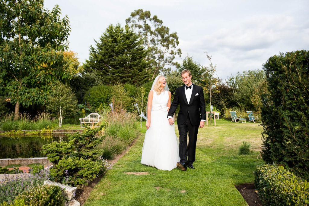 LGBT wedding photography, elegant bride and groom walk in gardens hand in hand