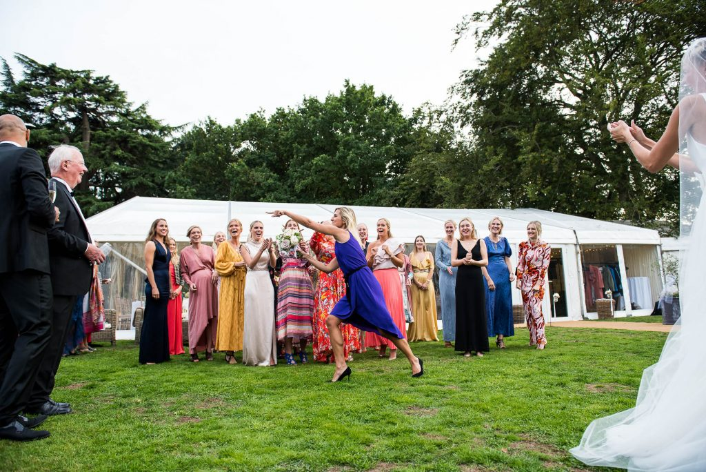 LGBT wedding photography, wedding guest catches the bouquet and points at partner