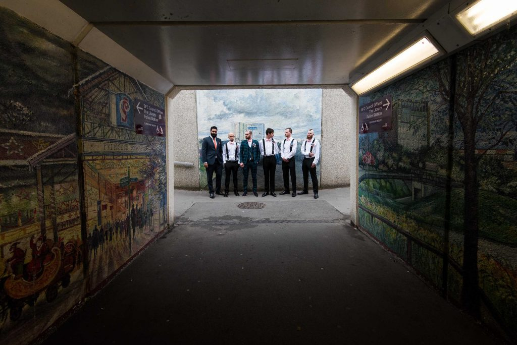 Groomsmen and groom quirky photograph in a tunnel