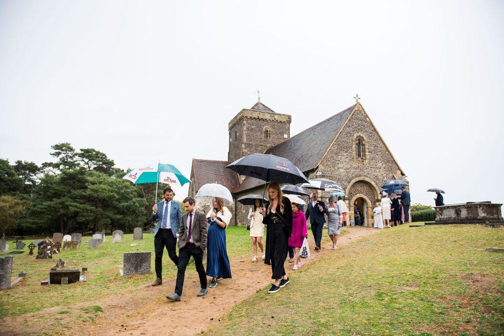 LGBT wedding photography, wedding guests leave ceremony under umbrellas for wet Surrey wedding