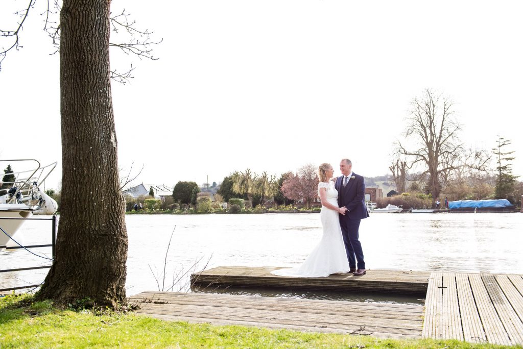 LGBT wedding photography, bride and groom pose by the river in Marlow