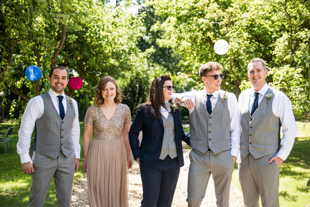 LGBT wedding photography, relaxed group wedding photography with bridesmaids and groomsmen laughing together