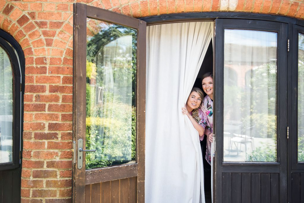 LGBT wedding photography, bridesmaids peer through curtain at Dodmoor House wedding venue