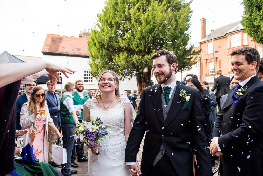 LGBT wedding photography,  newlywed couple walk down confetti aisle