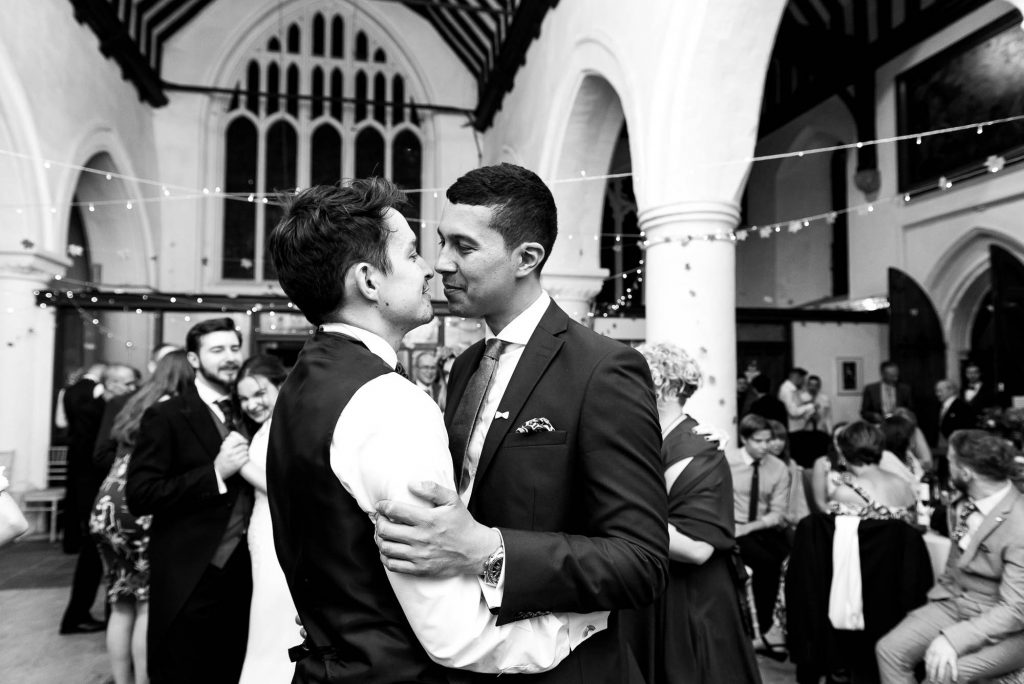 LGBT wedding photography, gay couple enbrace on the dance floor, black and white wedding photography