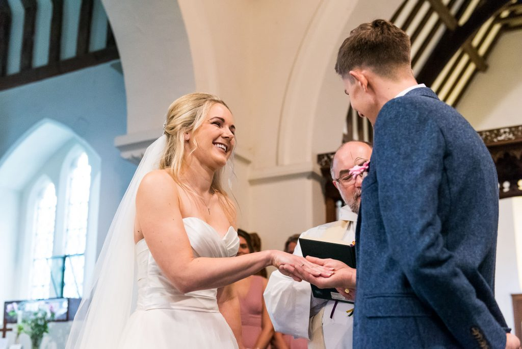 smiling bride takes the hand of her groom