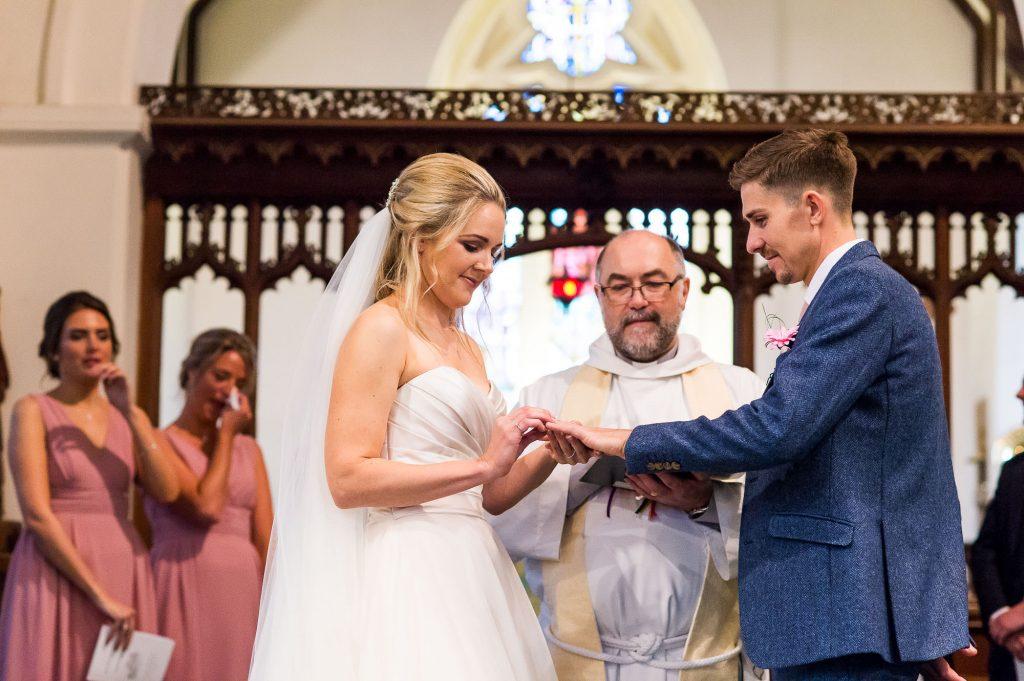 st martha's wedding, bride and groom exchange rings in wedding ceremony
