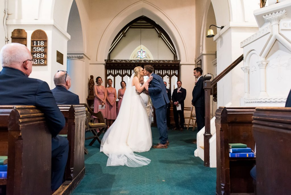 bride wearing a strapless dress shares a first kiss with her stylish groom