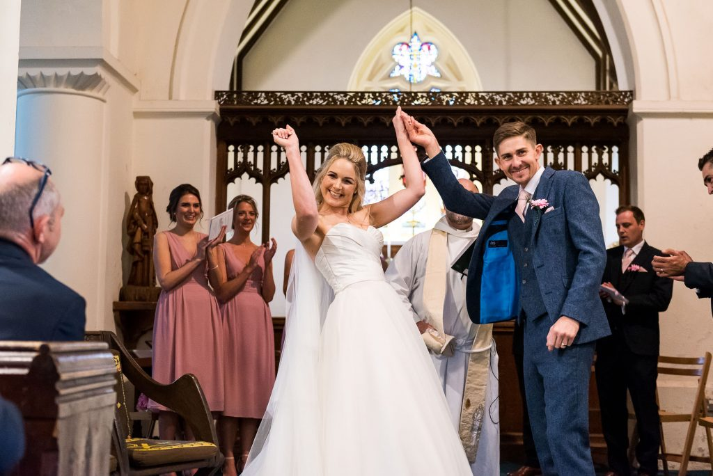 bride raises her arms in celebration after marriage ceremony