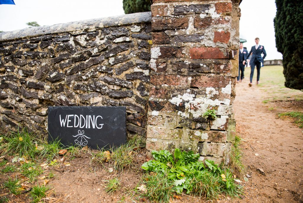 wedding sign up against a brick wall