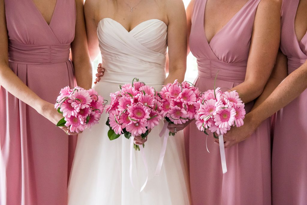 bride with her bridesmaids showcasing gorgeous matching bouquets of pink flowers